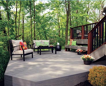 Wood deck surrounded by greent tress